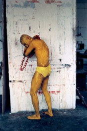Lee Wen, &quot;Journey of a Yellow Man No.1,&quot; 1992.Performance with red chain and solid fuel at City of London Polytechnic, London (April 1992). Image courtesy of artist.