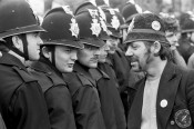 Picket wearing a joke police helmet talking to Police at Orgreave 1984–85 miners strike. Photo © Martin Jenkinson.